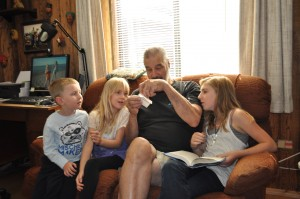 This is me with my grandpa, my brother, and sister looking at a present from my great grandma